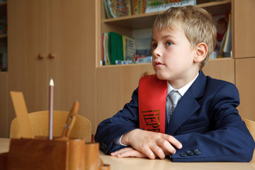 First class. Boy in school uniform at his desk.