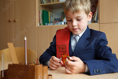 First class. Boy in school uniform at his desk, pen in hand.