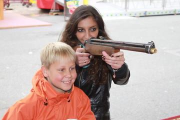 Junge Frau mit kleinem Jungen an einer Schießbude