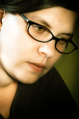 girl with glasses on dark background