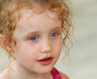 A Little Girl with Big Blue Eyes and Ringlets in Her Hair