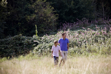 A father and son walking through a field