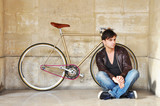 Young man sitting in front of his fixed-gear bicycle