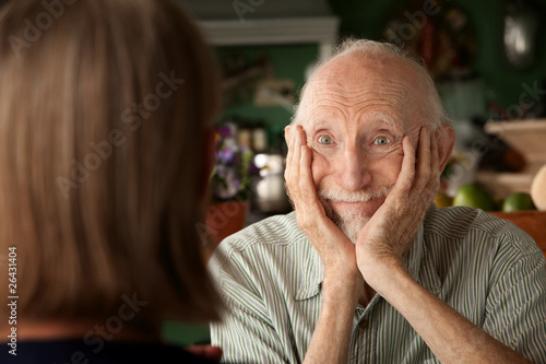 Senior couple at home focusing on man