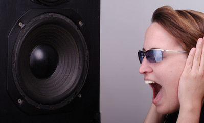 Young woman going crazy about loud music