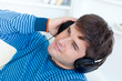 happy young man with headphones relaxing with music on the sofa