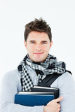 Young man wearing a scarf squeezing books against himself