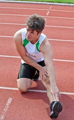 young male sprinter streching on the floor before a race in a st