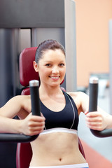 beautiful athletic woman using a bench press smiling at the came