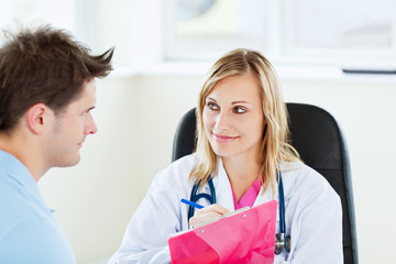 smiling doctor writing prescription during an appointment with a