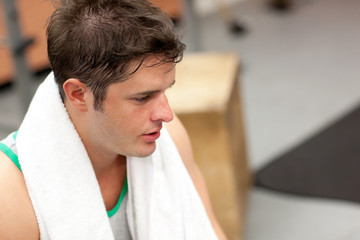 exhausted man with towel around the neck after exercises in a fi