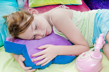 Young girl asleep by phone