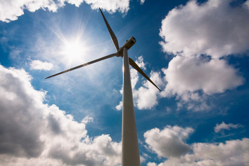Windmill against a blue sky and clouds, alternative energy sourc