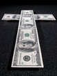 Cross figure is composed from dollars greenbacks in perspective