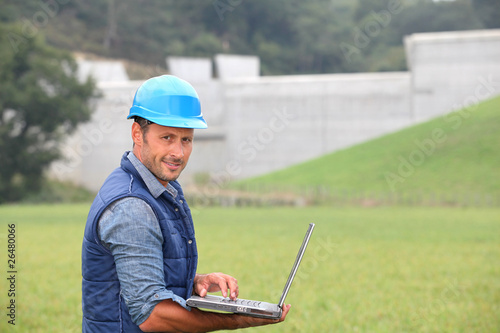 Engineer standing in front of dam under construction - 26480066