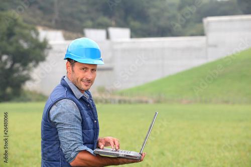 Foto op Canvas Dam Engineer standing in front of dam under construction