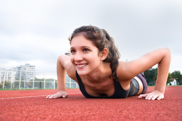 Girl doing push-ups on race track