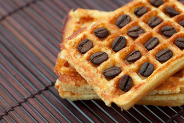 coffee beans and waffles on a bamboo mat