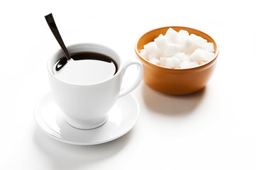 Cup of coffee and plate with sugar