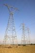 High voltage electricity pylons against blue sky