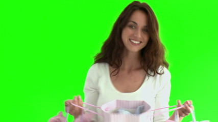 Happy woman holding shopping bags against green screen