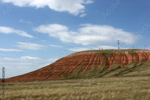 Steppe red clay hill against a blue sky