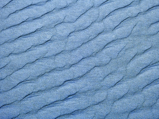 Abstract background of blue sand ripples at the beach