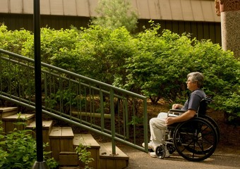 man in wheelchair contemplating a set of stairs