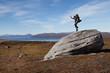 Springender Wanderer auf einem riesigen Felsbrocken