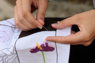 Woman hand embroiders