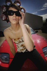 A Young Woman Sitting On The Hood Of A Sports Car