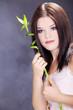 brünette Frau mit Bambus Pflanze blickt vertäumt