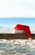 Red Santa's hat on wooden bench at the tropical beach