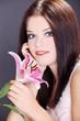 brünette beauty Frau blickt mit rosa Lilie