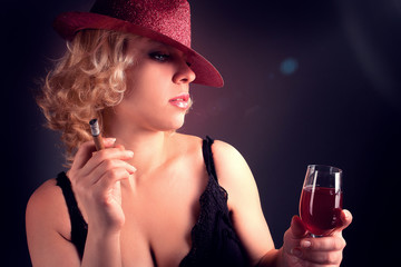 woman in hat with wine red in glass with sigar