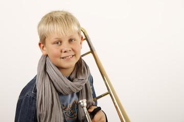 Portrait eines kleinen Jungen mit seiner Posaune