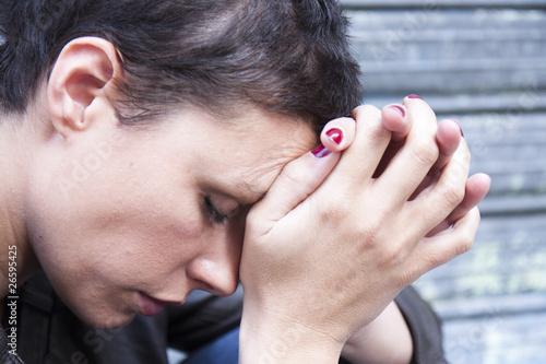 jeune femme fatiguée, la tête appuyée contre ses mains