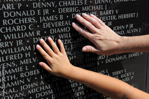 Hand of Adult and Child Touching Names at War Memorial