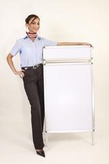 Attraktive Geschäftsfrau neben einem Kundenstopper