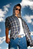 Young man urban fashion portrait over sky background
