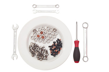 Gedeck aus Schrauben mit Werkzeugen als Besteck.