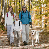 Family with dog on autumn trek poster