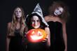 three halloween personages with orange pumpkin