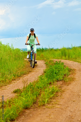 woman with bike on green field