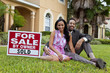 Happy African American Couple Beside House For Sale Sold Sign