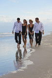 Four Young People, Two Couples, Holding Hands On A Beach