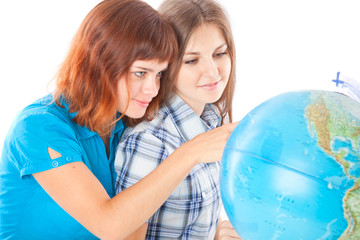 Two teen-girls are looking at globe