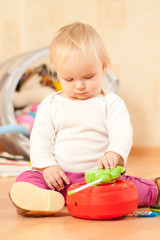 Adorable toddler girl play with portable radio on floor