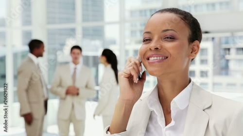 Beautiful Businesswoman on a Cellphone in an Office Lobby