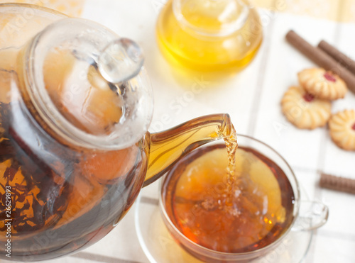 Plakat Hot tea flowing from teacup into glass mug